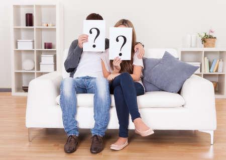 interrogativa: Pareja en la sala de estar con signos de interrogaci�n delante de sus caras