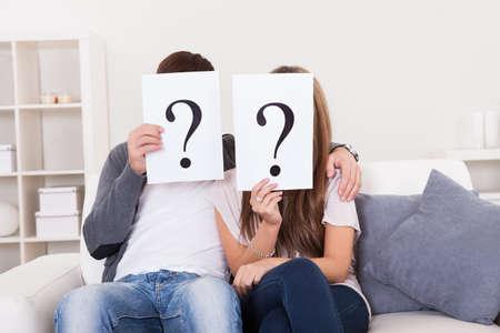 dudas: Pareja en la sala de estar con signos de interrogación delante de sus caras