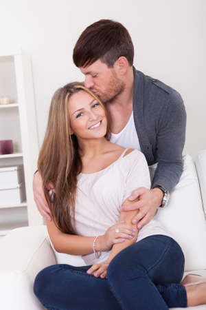 Loving young couple at home on the couch Stock Photo - 16522265