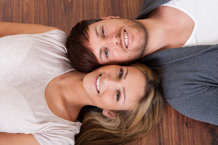 Friends lie alongside opposite heads on wooden floor. Stock Photo - 16521961