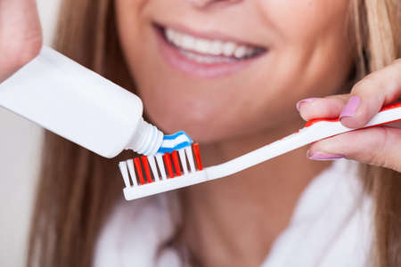 Mom put blue striped toothpaste on red & white toothbrush Stock Photo - 16522033
