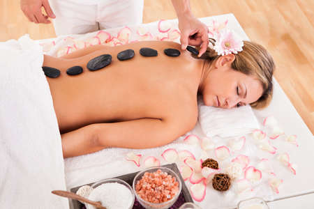 promotes: Hot stones lined on her back promotes relaxation.