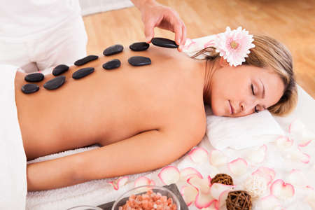 hot stone massage: Hot stones lined on her back promotes relaxation.