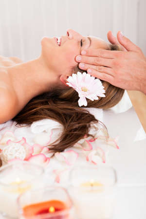Beautiful woman with a flower in her hair enjoying a spa treatment smiling as a beautician gently massages her temples Stock Photo - 16522142