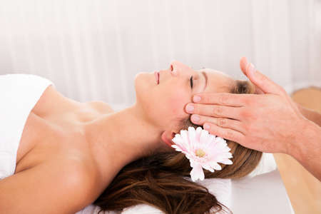 Beautiful woman with a flower in her hair enjoying a spa treatment smiling as a beautician gently massages her temples Stock Photo - 16522031