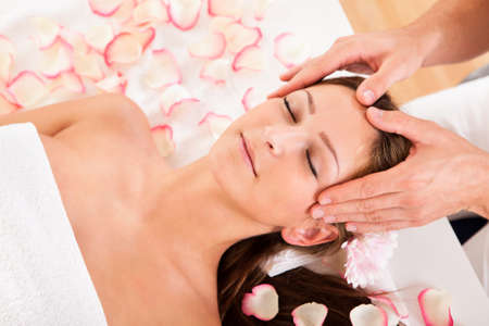 therapeutical: Beautiful woman with a flower in her hair enjoying a spa treatment smiling as a beautician gently massages her temples