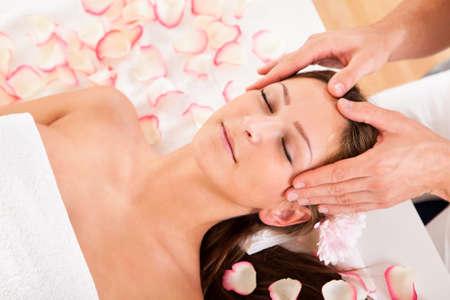 hair spa: Mujer hermosa con una flor en el pelo disfrutando de un tratamiento de spa sonriendo como esteticista masajea suavemente las sienes