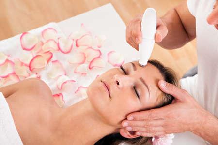 tratamiento facial: Mujer atractiva joven que se somete a tratamiento de microdermabrasi�n en el establecimiento spa Foto de archivo
