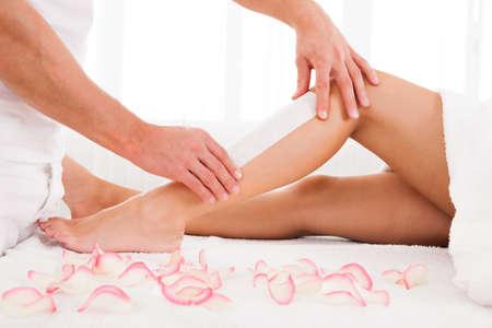 depilaciones: Depilaci�n Beautician una mujer pierna aplicaci�n de una tira de material sobre la cera caliente para eliminar los pelos cuando se tira Foto de archivo
