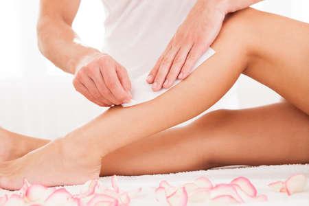 depilacion con cera: Depilación Beautician de una mujer pierna aplicación de una tira de material sobre la cera caliente para eliminar los pelos cuando se tira Foto de archivo
