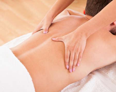 masaje deportivo: Hombre joven hermoso que miente en su est�mago en un spa con un masaje en la espalda Foto de archivo