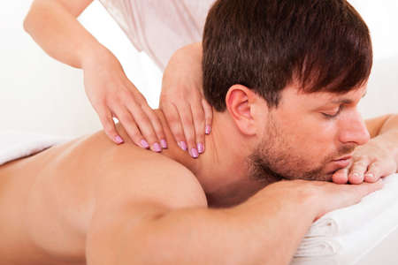 massage hands: Handsome young man lying on his stomach in a spa having a shoulder massage