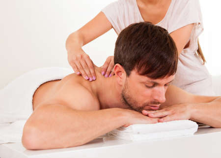 back strain: Handsome young man lying on his stomach in a spa having a shoulder massage