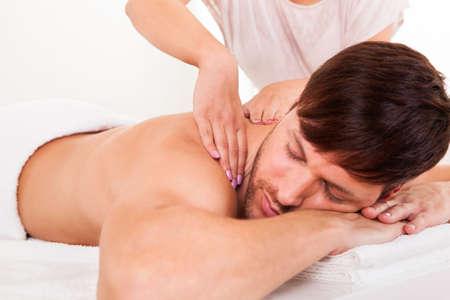 masaje deportivo: Hombre joven hermoso que miente en su est�mago en un spa con un masaje en los hombros