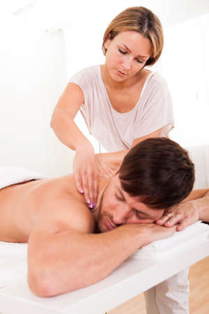 Handsome young man lying on his stomach in a spa having a shoulder massage photo