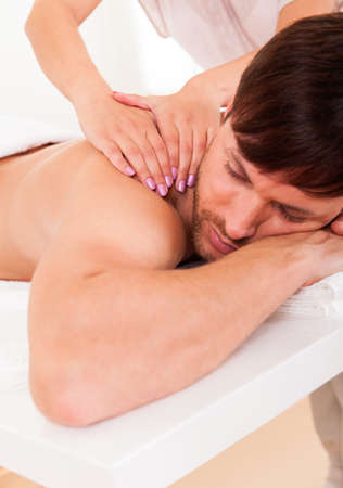 masaje deportivo: Hombre joven hermoso que miente en su estómago en un spa con un masaje en los hombros