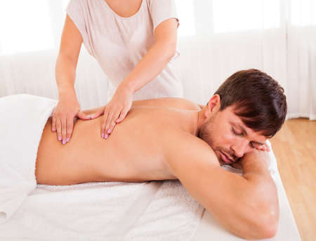 back massage: Handsome young man lying on his stomach in a spa having a back massage Stock Photo