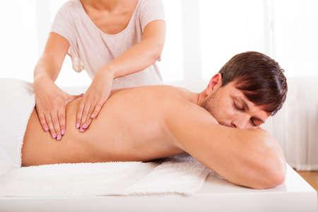 masaje deportivo: Hombre joven hermoso que miente en su estómago en un spa con un masaje en la espalda Foto de archivo