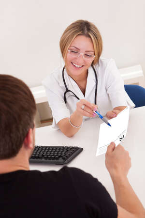 Doctor in clinic explains prescription for sick client. photo