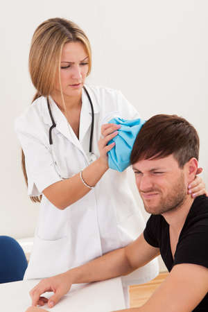 bumps: Cold pack in doctors right hand was applied to head. Stock Photo