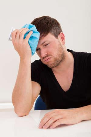 sobrio: Sober chico guapo joven tiene dolor de cabeza y aplicar una bolsa de hielo