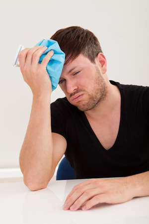 Sober young handsome guy got headache and applying ice bag Stock Photo - 16522114