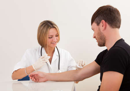 samples: Nurse making injection to patient in clinic Stock Photo