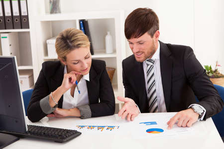Business partners discuss sales basing through graphs. Stock Photo - 16522046