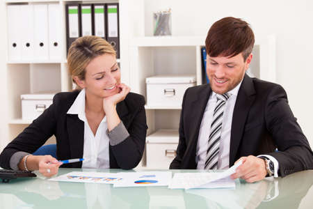 Business partners discuss sales basing through graphs. Stock Photo - 16522078