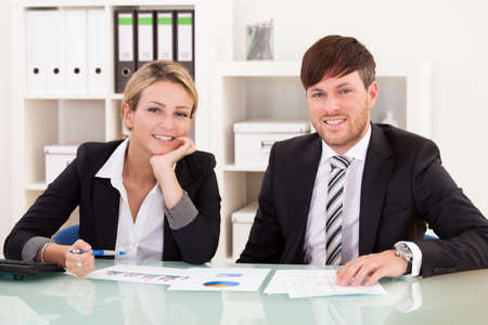 Business partners discuss sales basing through graphs. Stock Photo - 16522081