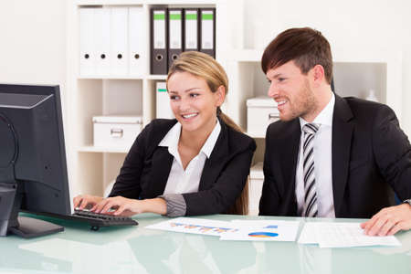 Business partners discuss sales basing through graphs. photo