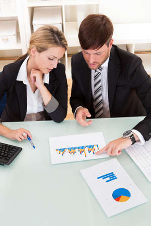 Business colleagues sitting together at a table in an office discussing and analyzing a bar graph Stock Photo - 16522203