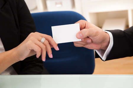 hand business card: Cropped image of the hands of a business man handing over a blank white business card to a woman ready for your contact information Stock Photo