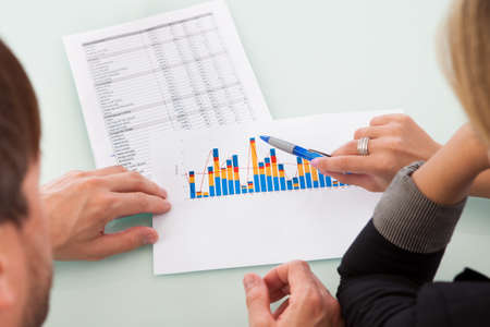 high performance: Over the shoulder view of two business partners discussing a colorful fluctuating bar graph comparing it with a text table