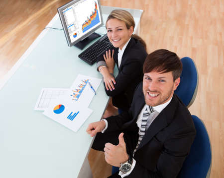 Over the shoulder view of two business partners discussing a colorful fluctuating bar graph comparing it with a text table Stock Photo - 16522150