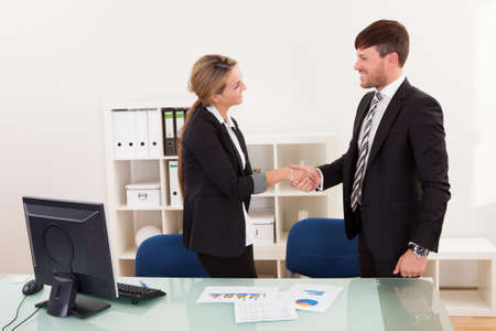A successful smiling business man and woman stand in an office behind a table shaking hands as they successfully conclude a deal photo