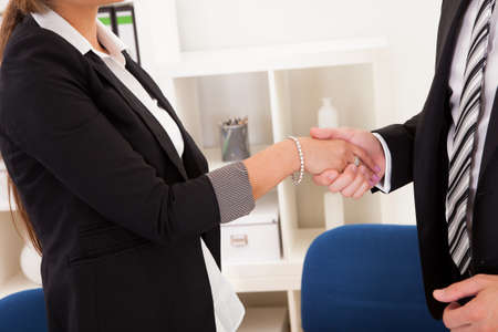 conclude: A successful smiling business man and woman stand in an office behind a table shaking hands as they successfully conclude a deal