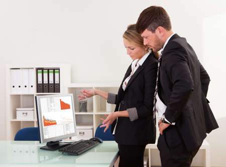 Two professional young business colleagues stand in an office looking at a computer with dropping descending graphs photo