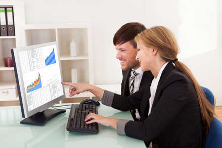 Business people looking at sales growth charts in the office Stock Photo - 16522059