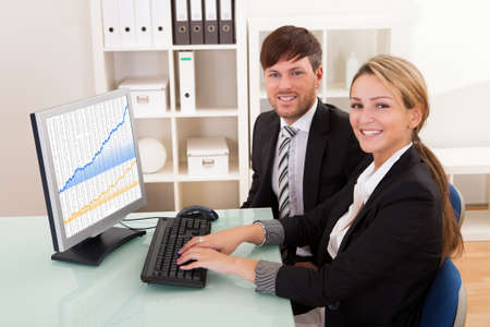 Business people looking at sales growth charts in the office Stock Photo - 16522135