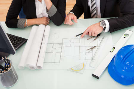 engineer computer: Cropped overhead view of a male and female architect discussing a set of blueprints spread out on a table Stock Photo