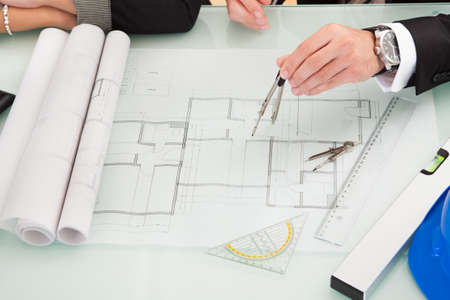 construction level: Cropped overhead view of a male and female architect discussing a set of blueprints spread out on a table Stock Photo