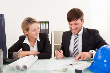 Attractive young architects working on their blueprint Stock Photo - 16522324