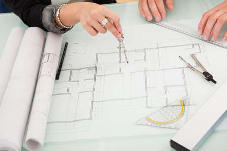 structural engineers: Cropped overhead view of a male and female architect discussing a set of blueprints spread out on a table Stock Photo