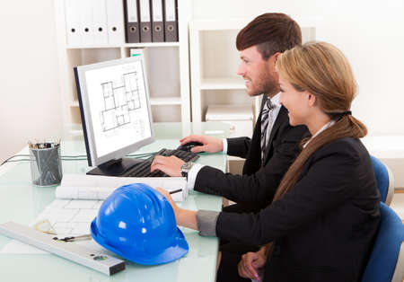 Two professional architects or structural engineers sitting at a desk looking at a computer discussing a building plan photo