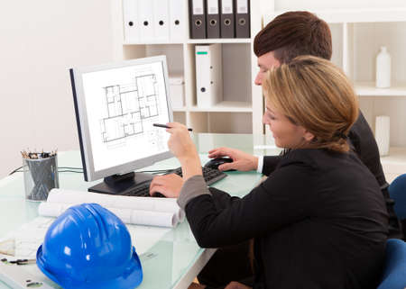 safety: Two professional architects or structural engineers sitting at a desk looking at a computer discussing a building plan Stock Photo