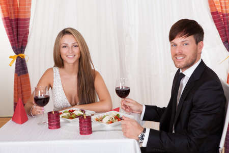 Young couple seated at a restaurant table enjoying a romantic dinner by candlelight and drinking red wine Stock Photo - 16522287