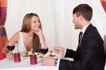 Attractive loving couple enjoying a romantic meal by candlelight at a stylish restaurant as they celebrate Valentines or their anniversary Stock Photo - 16522121