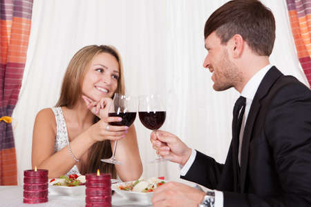 Romantic couple enjoying a meal at an elegant restaurant toasting each other with glasses of red wine Stock Photo - 16522035