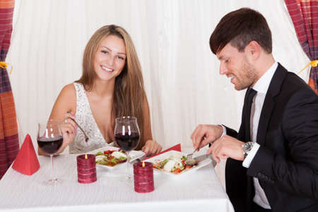Young couple seated at a restaurant table enjoying a romantic dinner by candlelight and drinking red wine photo